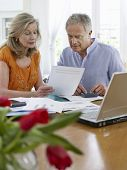 Mature couple looking at bills with calculator and laptop