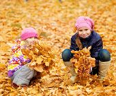 Children in autumn park. Kids with leaves