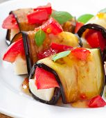 Eggplant rolls stuffed with cheese with a slice of tomato