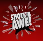 The words Shock and Awe breaking through glass to illustrate an overwhelming show of force or power as a surprise to an audience or opponent