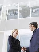 Low angle view of a businessman and woman shaking hands in office atrium