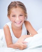 happy little cute girl woke up in white bed