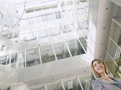 Low angle view of a smiling businesswoman standing in atrium of office building