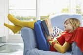 Side view of a relaxed young boy in superhero costume reading book on armchair