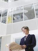 Low angle view of a businesswoman reading newspaper in atrium of office building