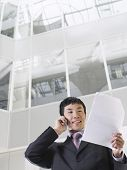 Businessman using mobile phone in atrium of office building