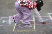 pic of hopscotch  - Side view of young girl playing hop - JPG