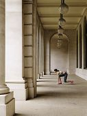 Full length side view of a female runner crouching in starting position in portico