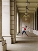 Full length of a female athlete throwing javelin in portico