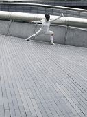 Full length of a female fencer lunging outdoors