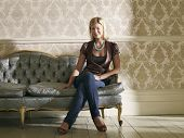 Full length portrait of a young woman sitting on sofa against wallpaper