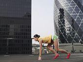 Volle Länge-Seitenansicht des weiblichen Läufer in Startposition gegen Innenstadt von Gebäuden in London