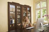 stock photo of shelving unit  - Yawning young blond woman using computer in study room at home - JPG