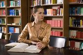 picture of shelving unit  - Young woman with book sitting at desk in library - JPG