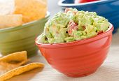 A red bowl filled with guacamole, a green bowl filled with chips and a blue bowl in the background.