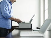 stock photo of cartridge  - Side view midsection of a mature man using printer at study table in house - JPG