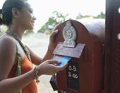 Side view of a smiling young mixed race woman putting postcard into mailbox
