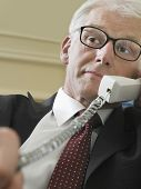Closeup of a middle aged businessman using landline phone