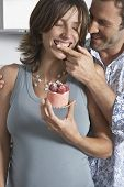 Man feeding cheerful pregnant woman strawberry shortcake in the kitchen