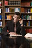 picture of shelving unit  - Thoughtful young man in formals with book and pen at desk in library - JPG