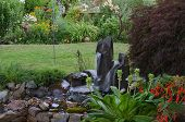 picture of garden sculpture  - A serene backyard retreat with twin fountains in the foreground and a county garden in the background with several pieces of art nestled among the flowers - JPG