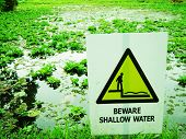 Beware of shallow water sign - pond