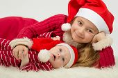 Smiling little girl with cute baby boy lie in the hats of Santa Claus