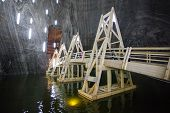 Underground Wood Bridge Over Lake In Turda Salt Mine