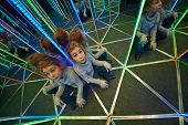 Little girl sits at crossing in mirror labyrinth illuminated with color lights