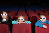 Mother with their son and daughter in 3D glasses in the cinema
