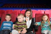 Mother with two sons and daughter in  the cinema, focus on mother
