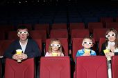 Parents with son and daughter in 3D glasses with popcorn in the cinema