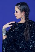 portrait of a beautiful brunette woman wearing sequin vintage jacket and diamond accessories against a blue studio background