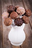 Homemade chocolate cake pops in a white jug. Vintage effect on old wood table.