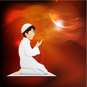 Young Muslim boy in traditional dress praying (Namaz, Islamic prayer) in shiny moon light night for