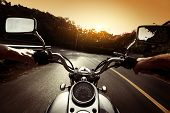 stock photo of reflection  - Driver riding motorcycle on an asphalt road through forest - JPG