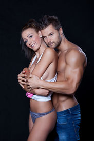 stock photo of breast-stroke  - Young muscular man holding a young woman from behind - JPG
