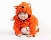 Baby boy in fox costume looking at camera on white