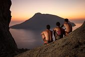Three rock climbers having rest at sunset