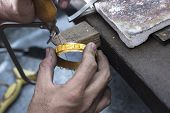 stock photo of bangles  - Close up of Jeweler crafting golden bangle with flame torch - JPG