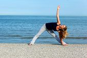 Athletic Woman Doing Yoga Exercises At The Seaside