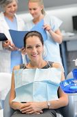 Businesswoman sitting chair dental surgery dentist checkup assistant in background