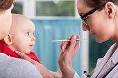 Doctor Examining Baby With Spatula