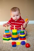 Baby boy playing with stacking learning toy