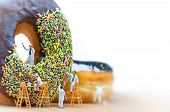 stock photo of figurines  - Group of painters painting over huge donut. Macro photo