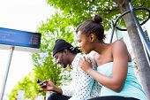 African man and girlfriend waiting at bus station