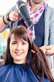 Hairdresser blow dry woman hair in shop