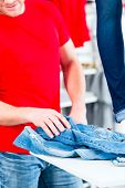 Man buying blue jeans in shop