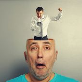 surprised senior man with small angry businessman in his head over grey background