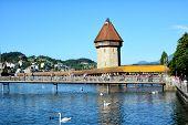 LUCERN, SWITZERLAND - July 4, 2014: Chapel Bridge or Kapellbrucke is the oldest wooden covered bridge in Europe. The 170 meter bridge spans the Reuss River.